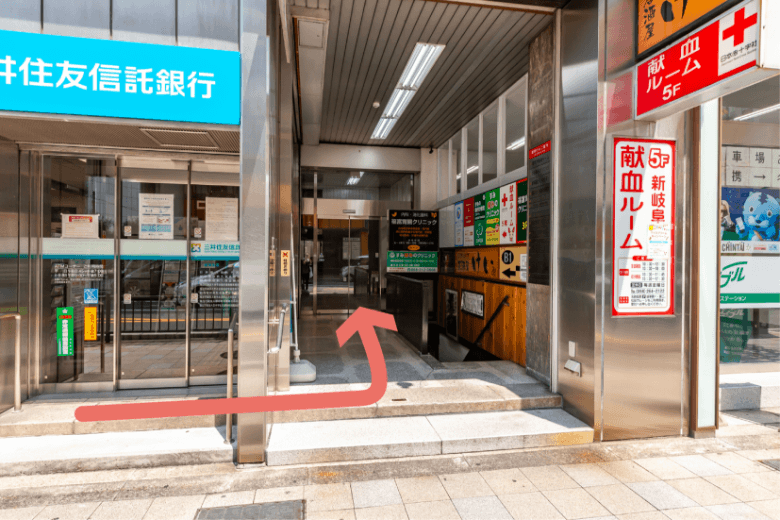 銀行と不動産屋さんの間にビル入口があります。